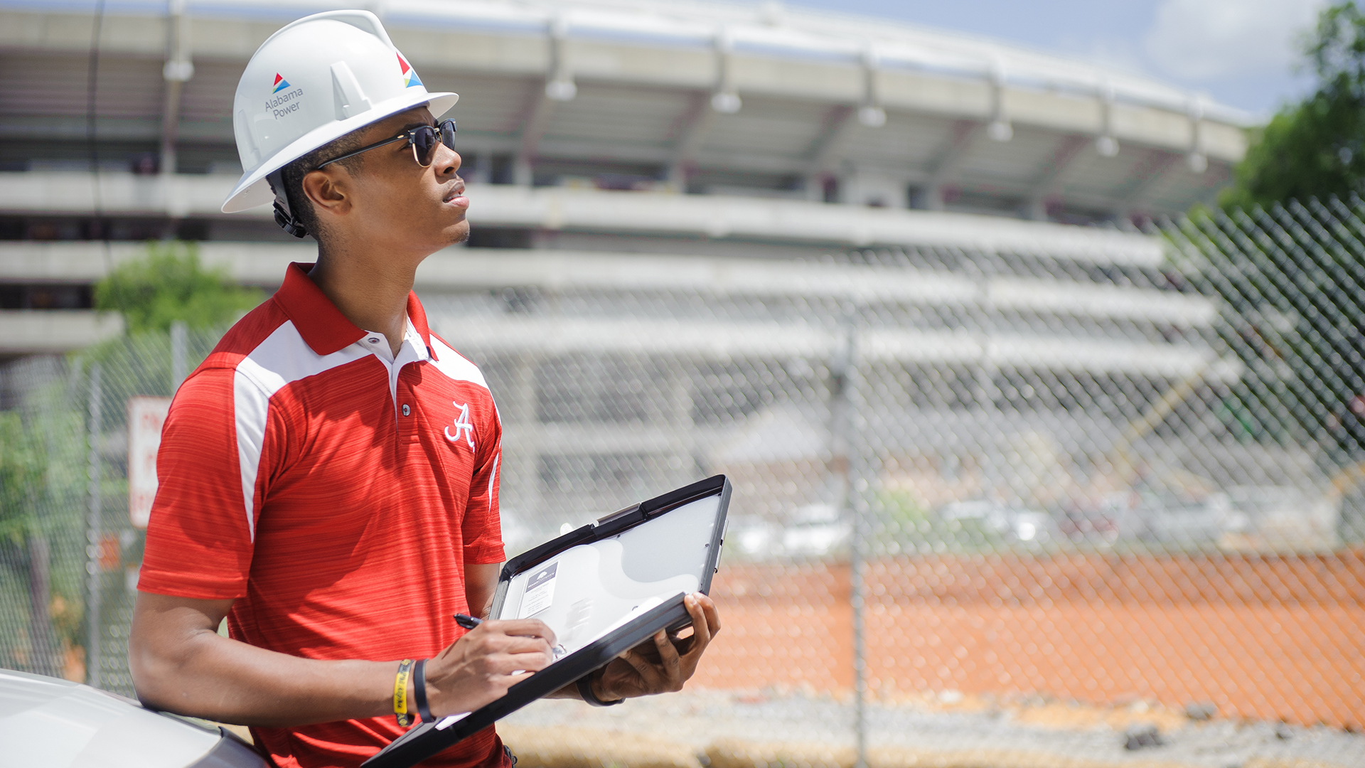 A student working in hard hat outside the Stadium.