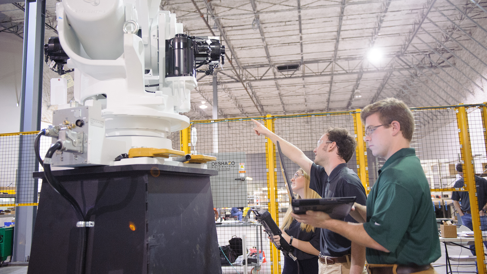 Three people look up at a big piece of machinery in a lab.