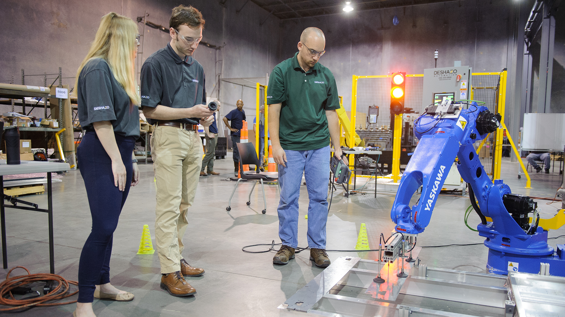 Two students and a professor watch a robot work.