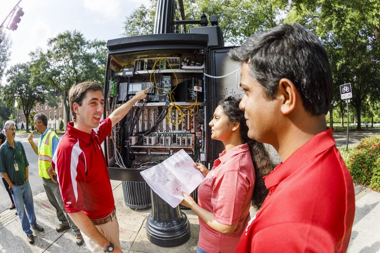 Professor and students looking into the inner workings of a traffic light.
