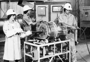 Black and white photo of studens gathered around a piece of machinery