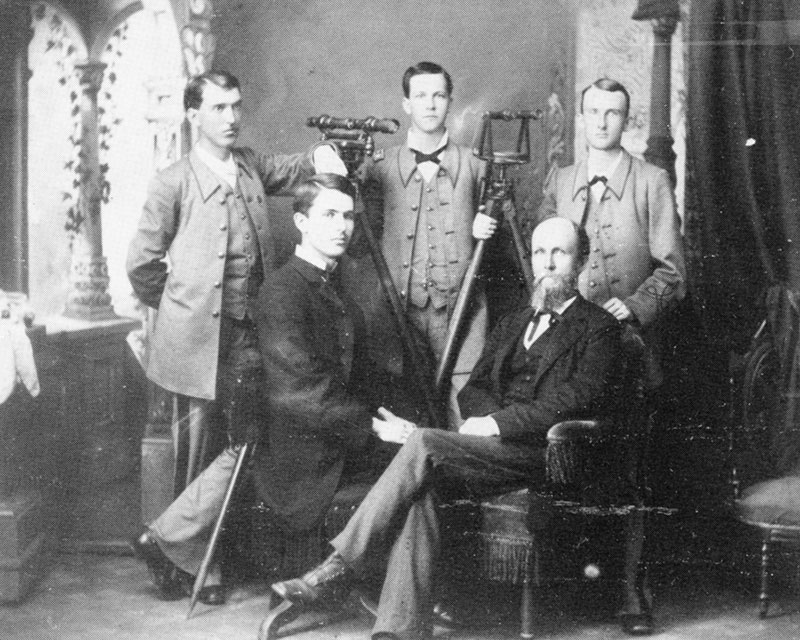 Old picture of five men, two seated.