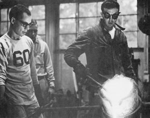 Black and white photo of three male students pouring metal