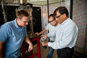 Color picture of Dr. Agrawal and two students looking at a machine part