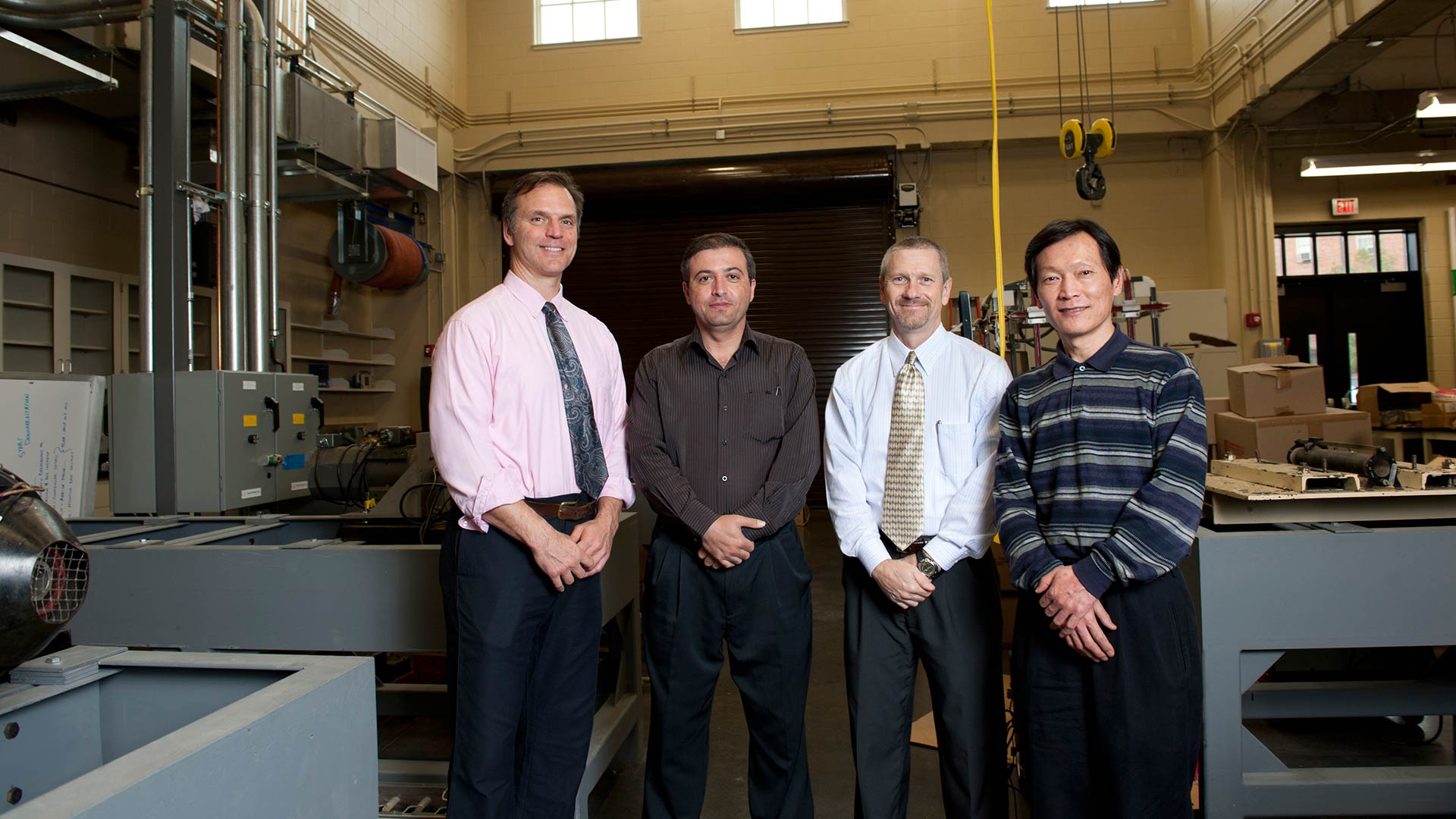 A group of 4 faculty stand in a lab.