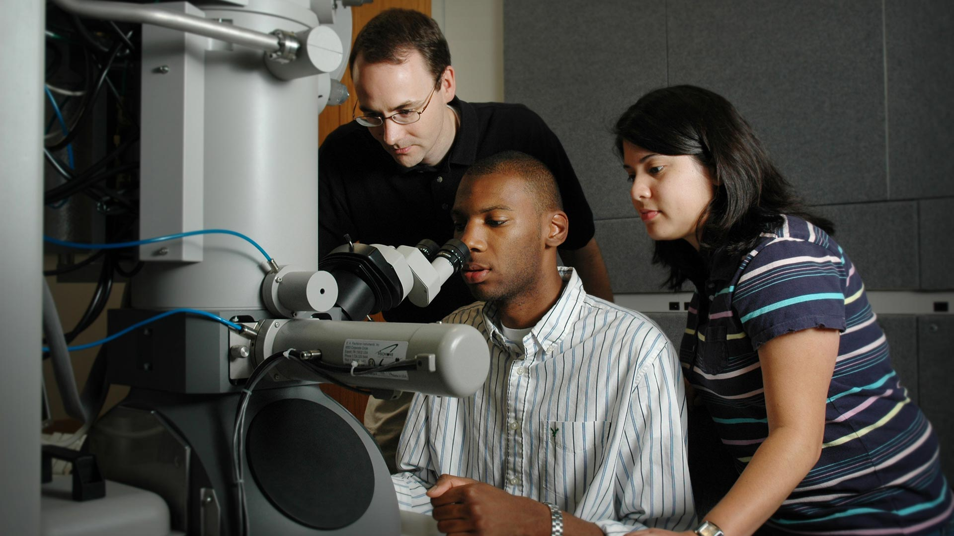 Three students looking into a huge microscope.