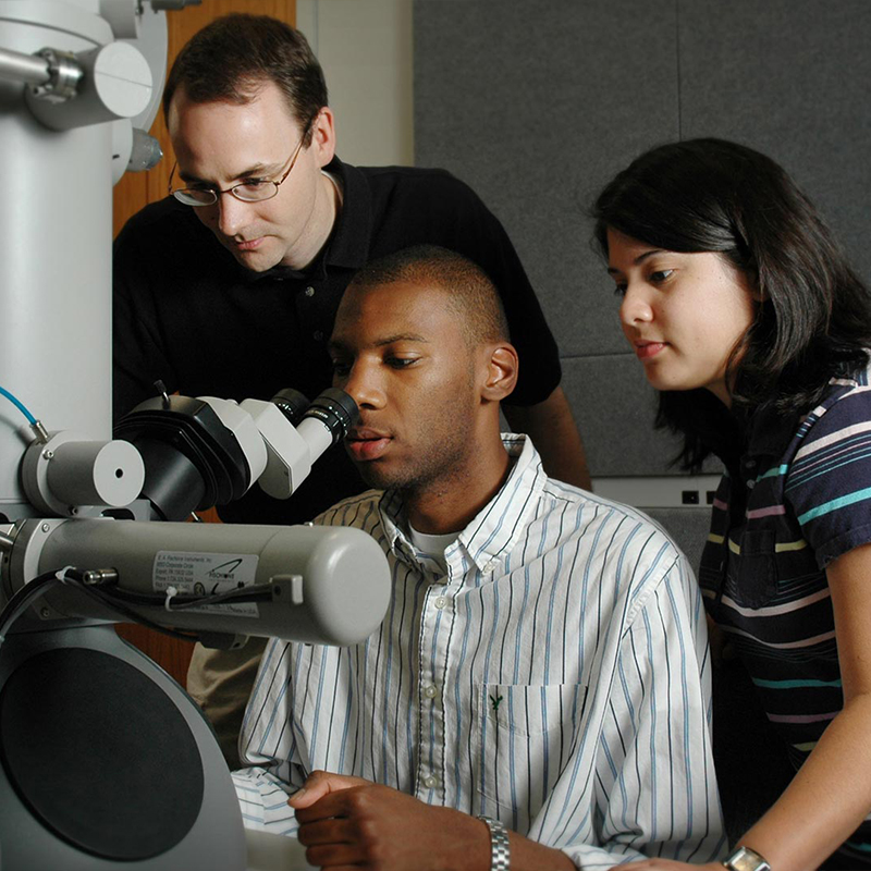 Three students look into a large microscope.