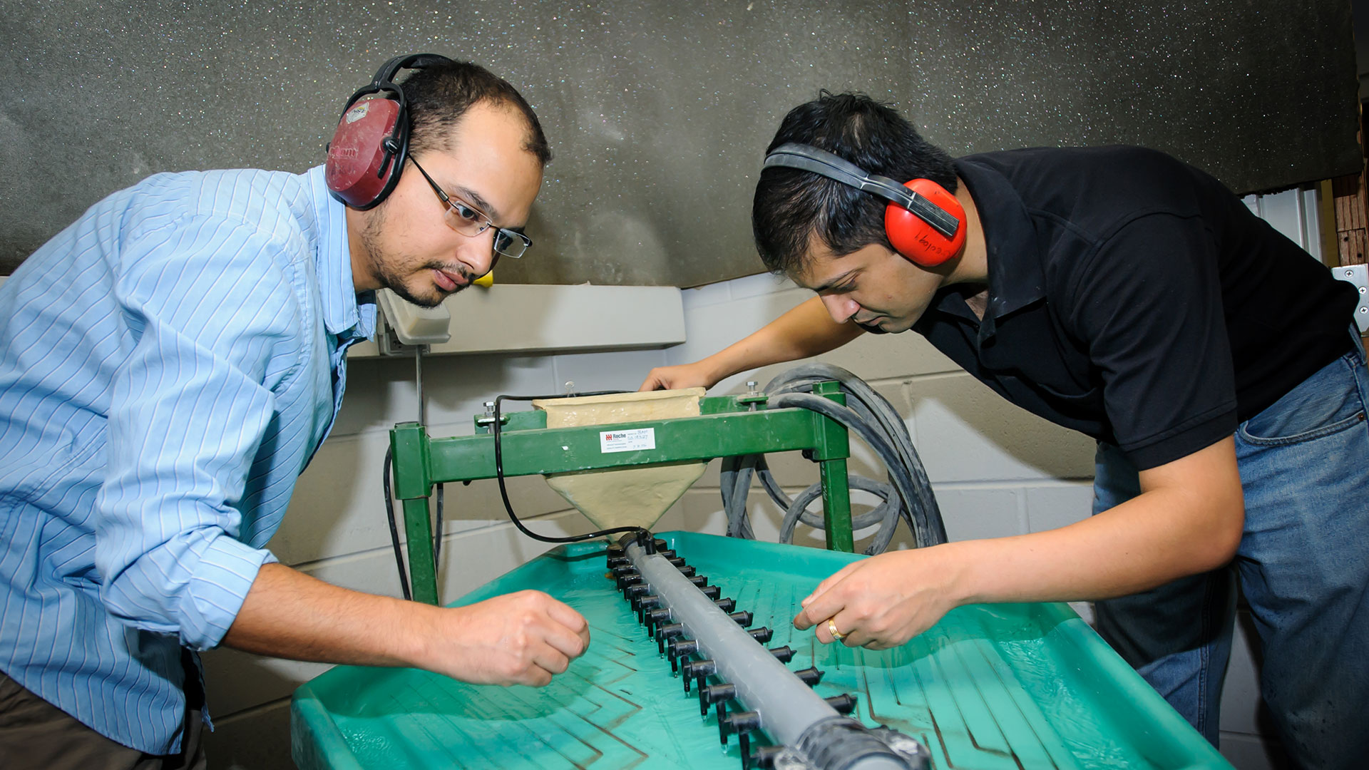 Two people with protective ear coverings work on a machine.