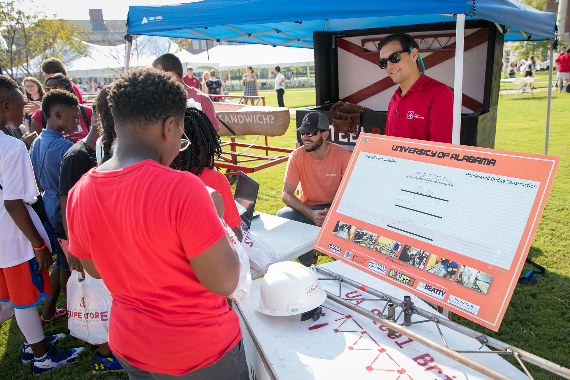 Students talk to kids at their stall on the Science and Engineering Quad during E-day