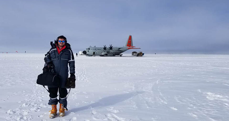 A person out in the tundra with an aircraft in background.