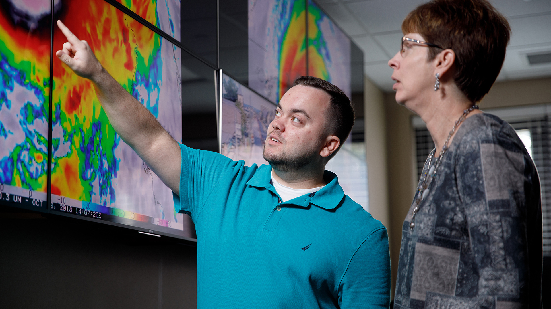 Two people look at a weather radar on screen.