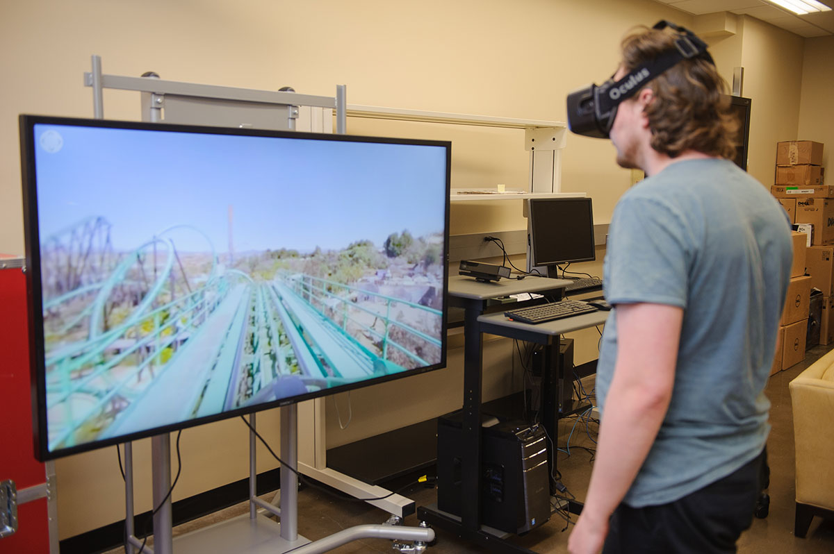 A student wears VR goggles while a TV plays a rollar coaster ride