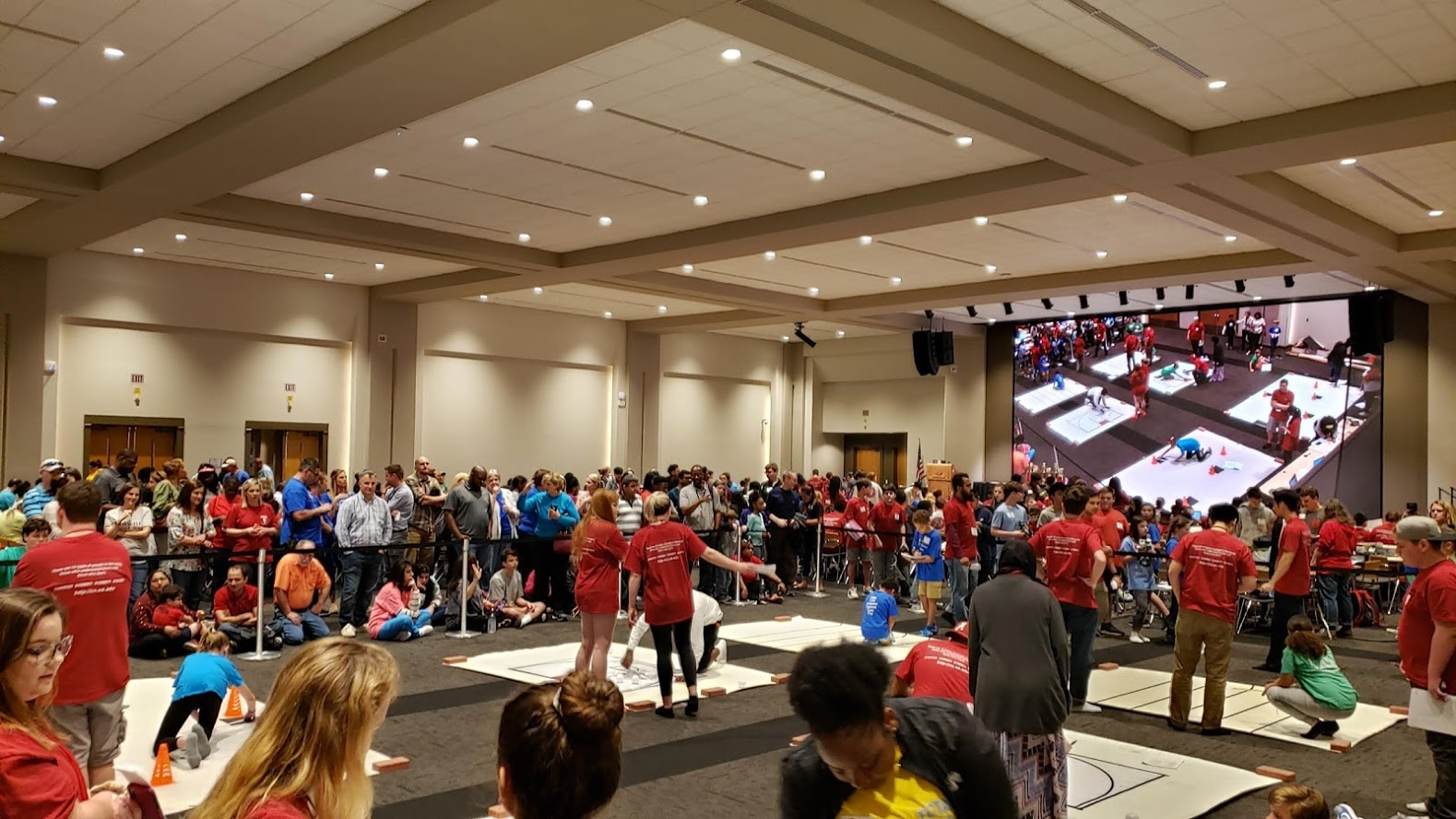 Huge room filled with kids and computer science students having a robotics competition