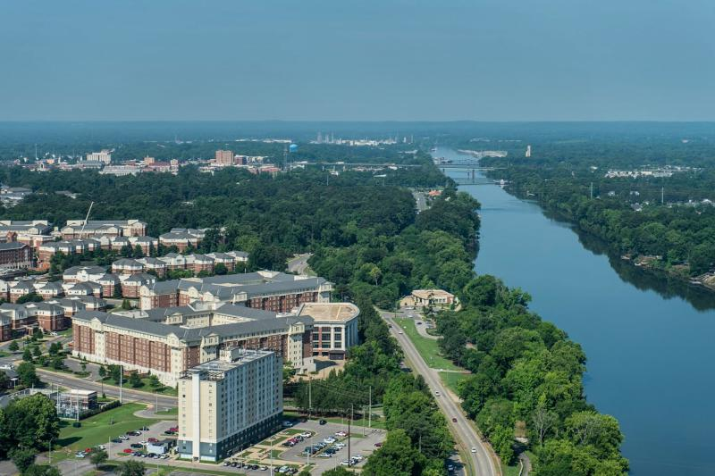 Ariel view of the Black Warrior River and buildings on campus next to it.