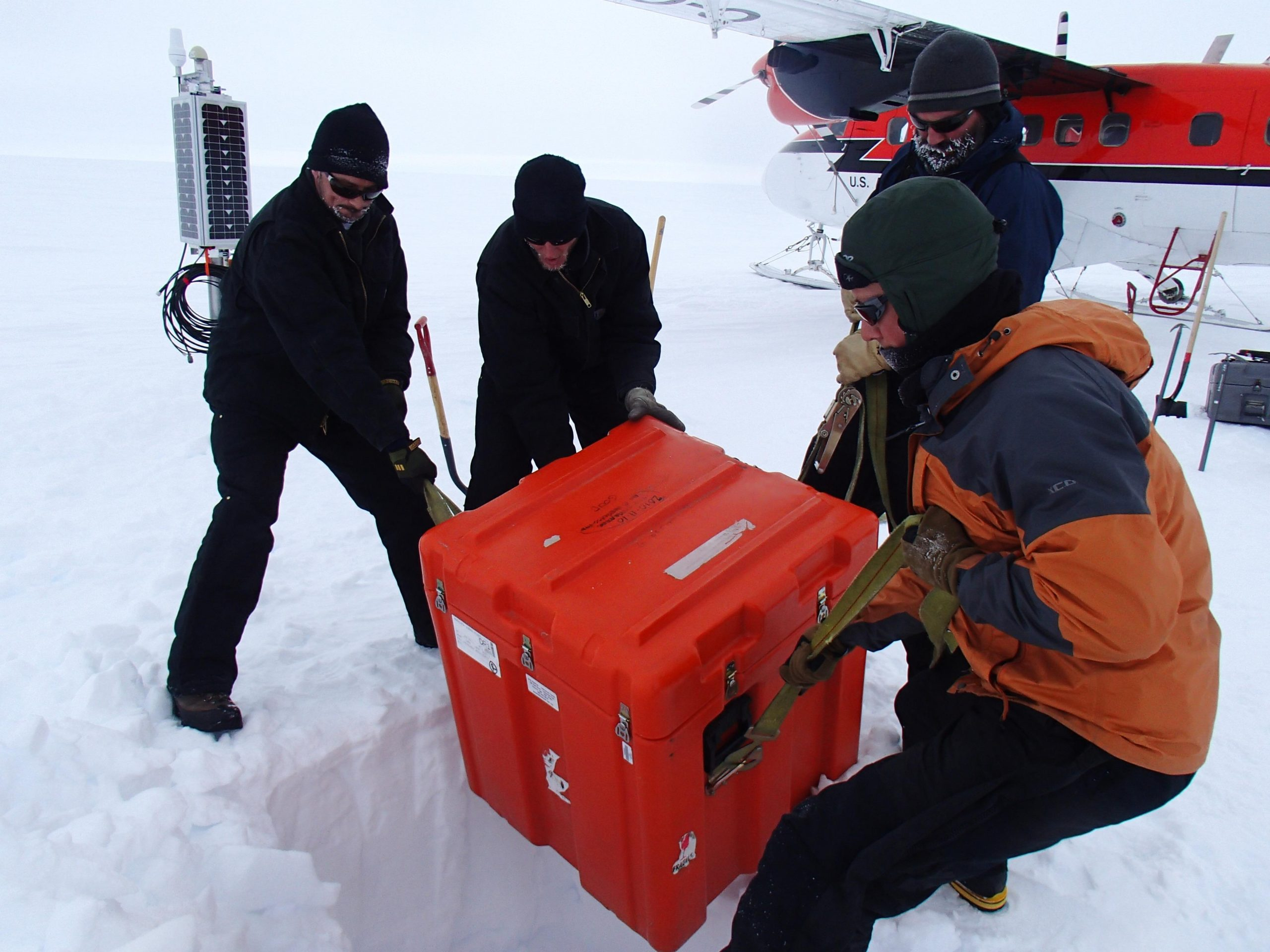 Twitter photo of people in a polar region lowering a box into the ice.