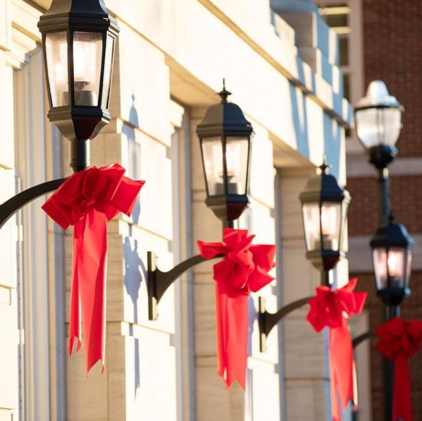 Instagram of lamps on a building with red ribbons on them.