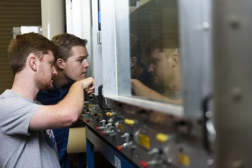 Two students peer through a window into the wind tunnel's inner workings
