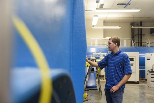 A student looking at the blue pipe of the wind tunnel