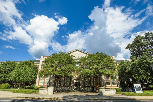 Far off shot of the front of Hardaway Hall with trees and blue sky with clouds.