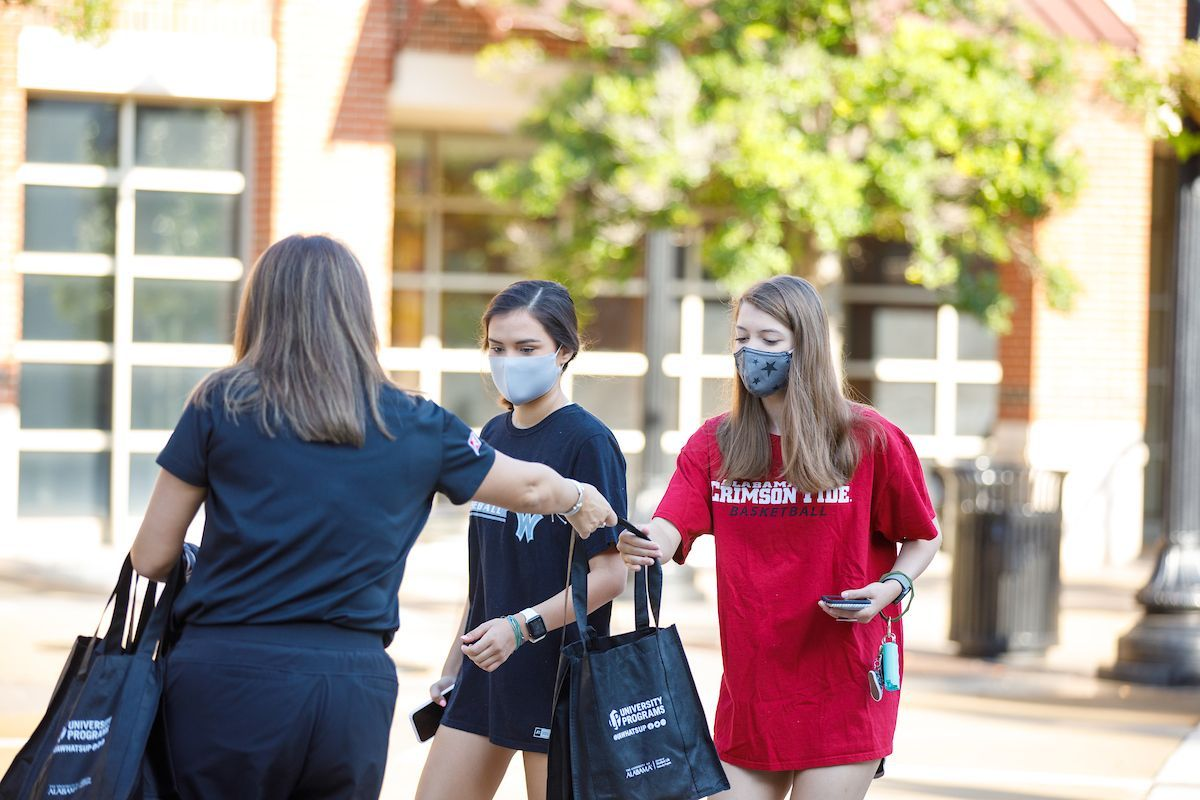 Twitter photo of a person passing out health bags to two students near the Ferg