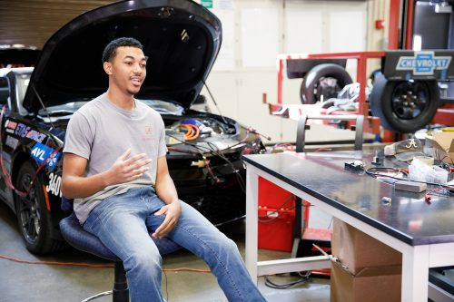 A Student talks about Eco Car while sitting in front of a car with the hood up and engine exposed.