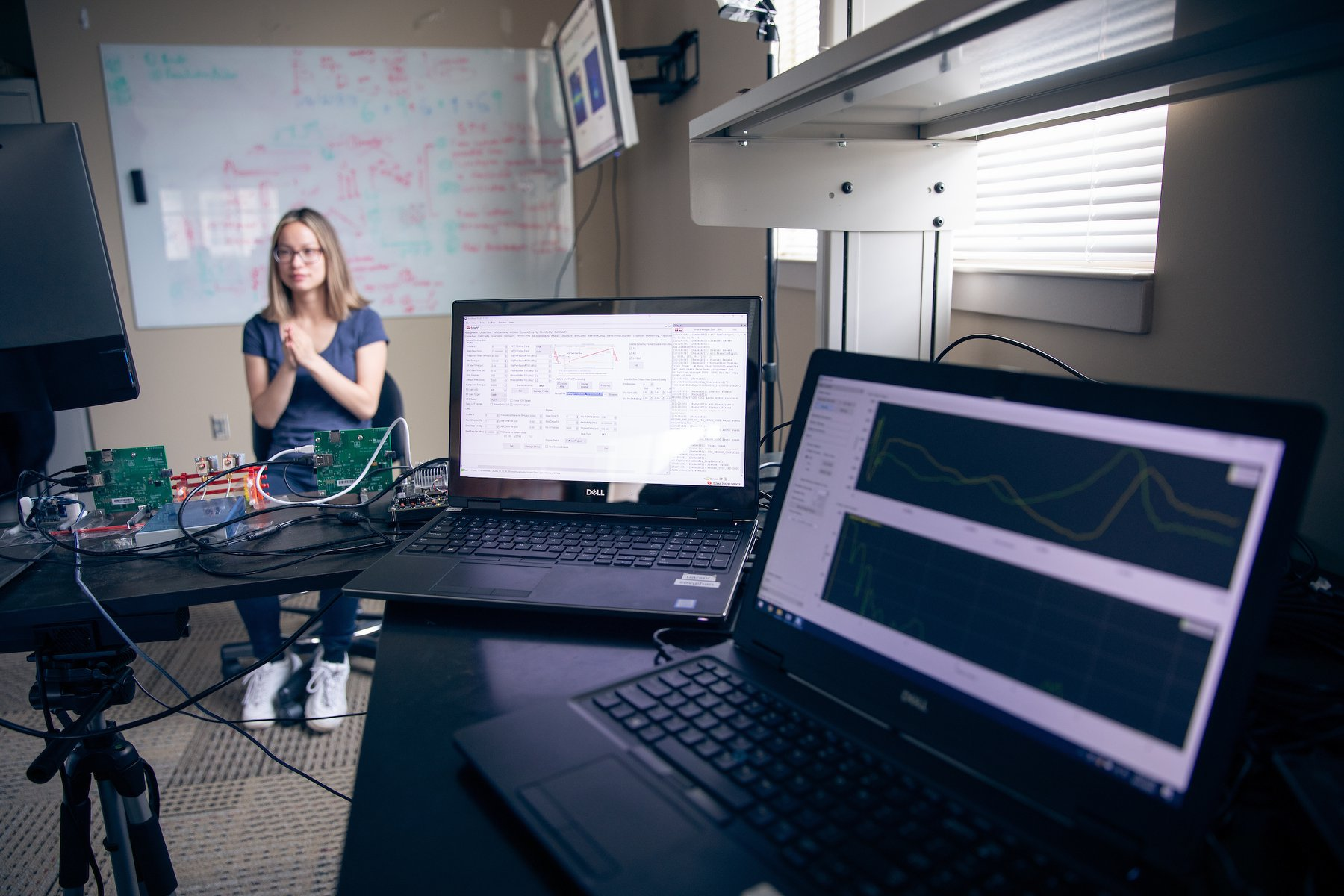Facebook photo of two laptops, wires, and a student sitting with whiteboard in background