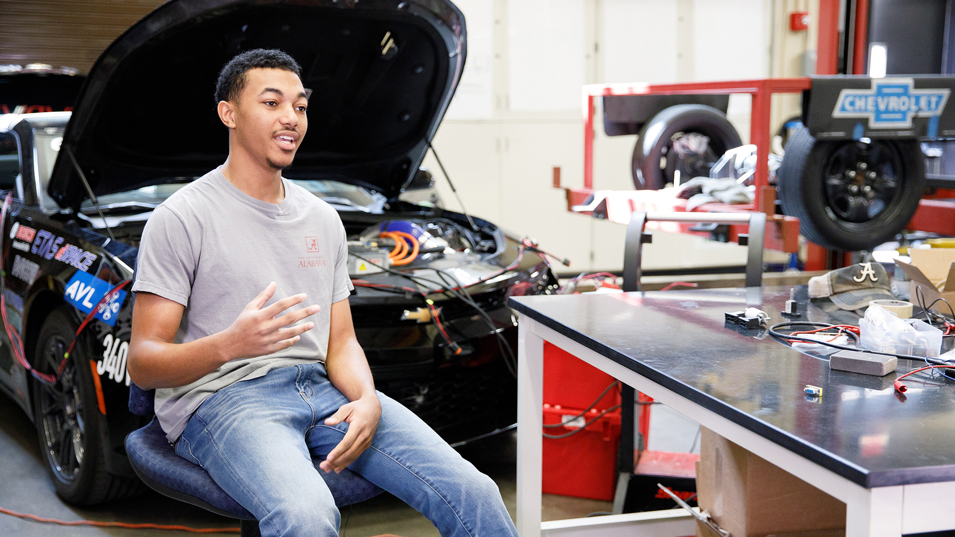 A black student sits beside a car with the engine visible