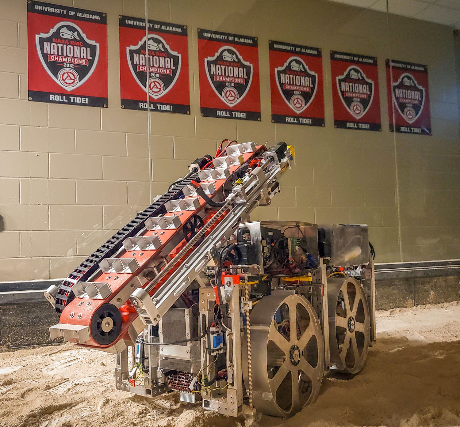 Twitter photo of a space rover robot in a room with sand