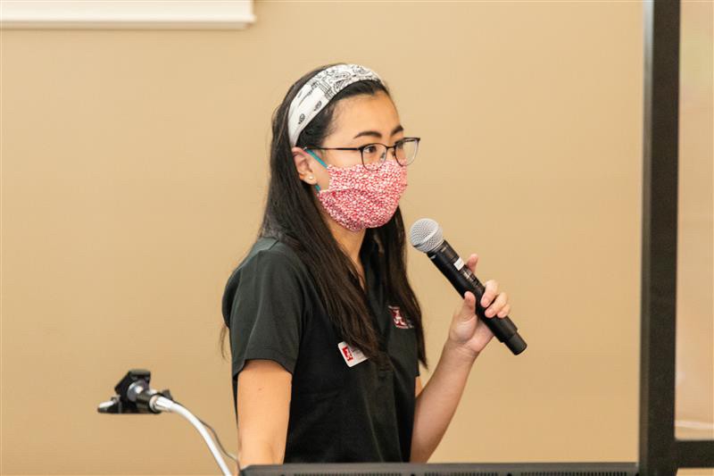 Instagram pic of a student with a microphone at a podium